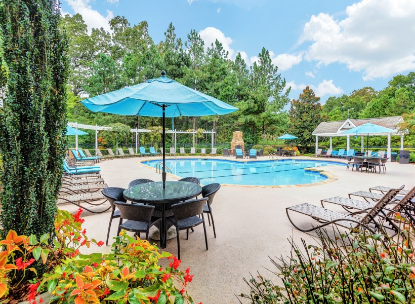 View of Pool Area, Showing Loungers, Outdoor Furniture, and Fireplace at Summer Park Apartments